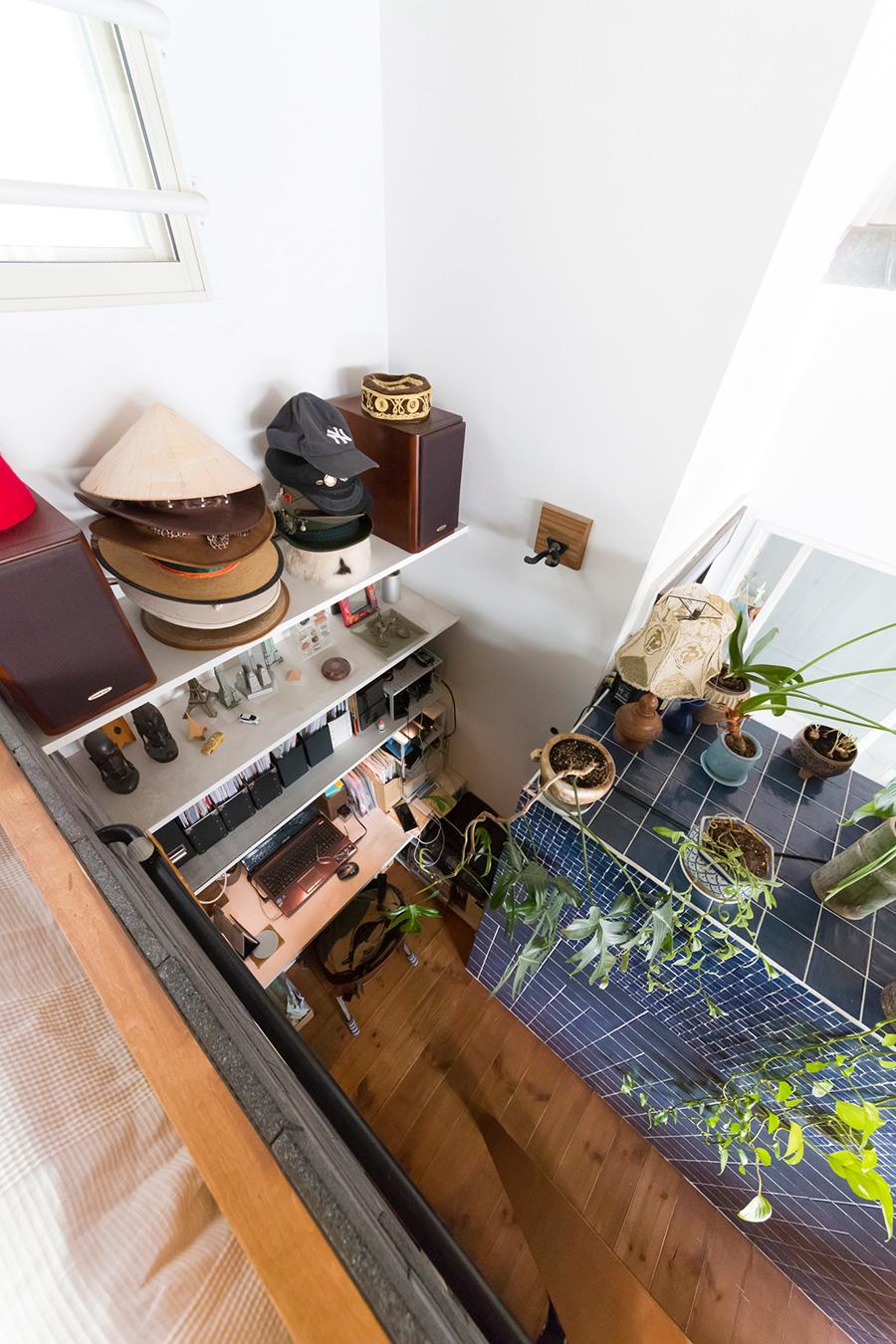 室内に誕生した路地を上から見下ろす。旅先で買い集めた帽子が棚の上に並ぶ。