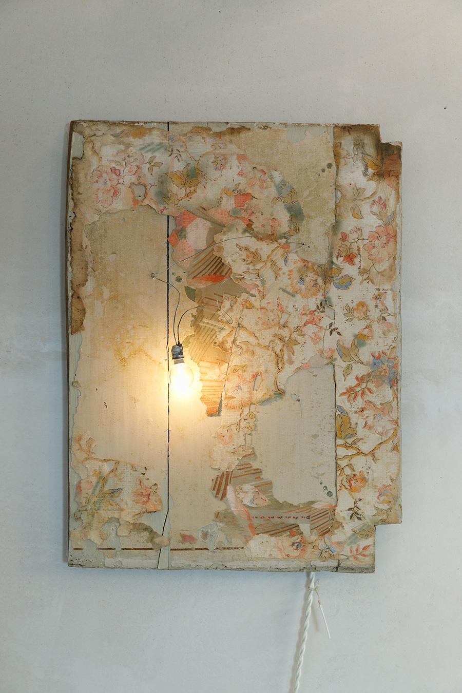 古い壁紙が残るボードに、電球をひとつ。ソケットから伸びるコードもアートのひとつになっている。