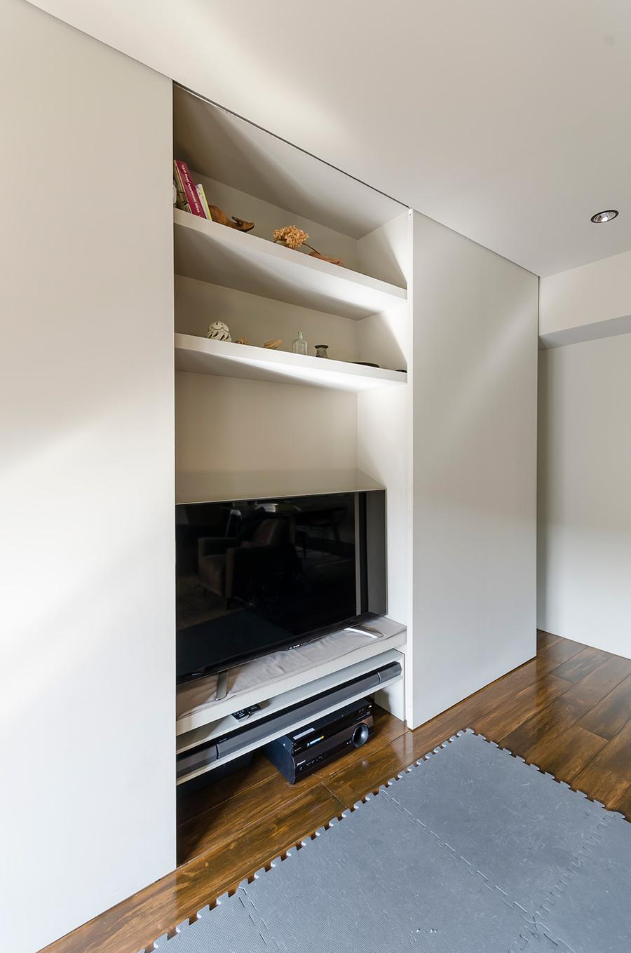 壁は、一度コンクリートをむき出して板を張り、塗装をかけた。悩みどころのテレビは壁面収納に。