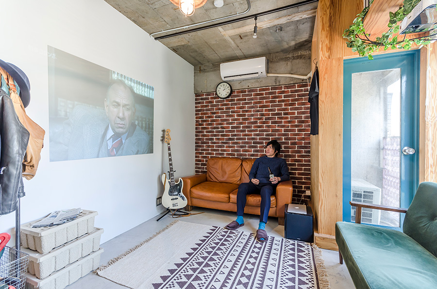 プロジェクターで壁に投影した映画を楽しむ内藤さん。