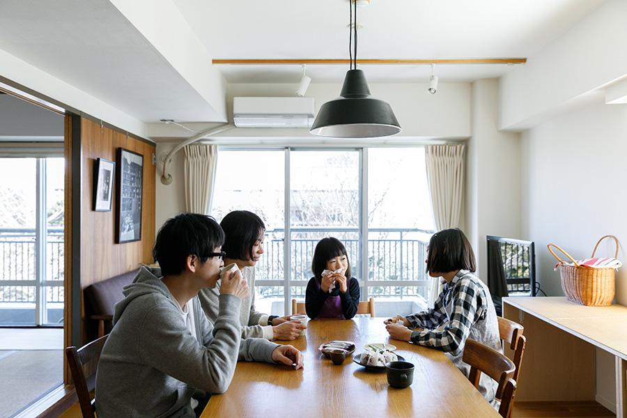 ダイニングテーブルでくつろぐ石川さん一家。テーブルはCIBONEで購入したもの。ランプはルイス・ポールセン。