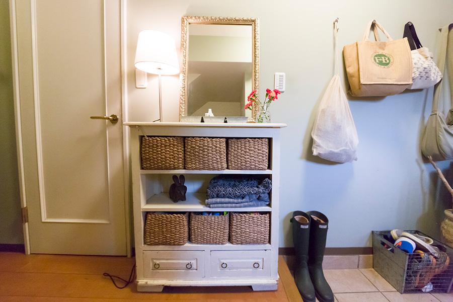 犬のお散歩セットなどを壁掛けに。外出時に必要なものを玄関脇に揃えている。棚は茶色から白に塗り替えた。