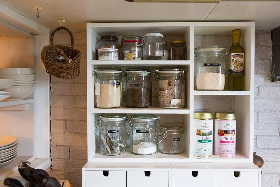 長く愛用しているガラス瓶の大きさに合わせて手作りした棚。キッチンの壁にはレンガタイルを貼ってもらった。