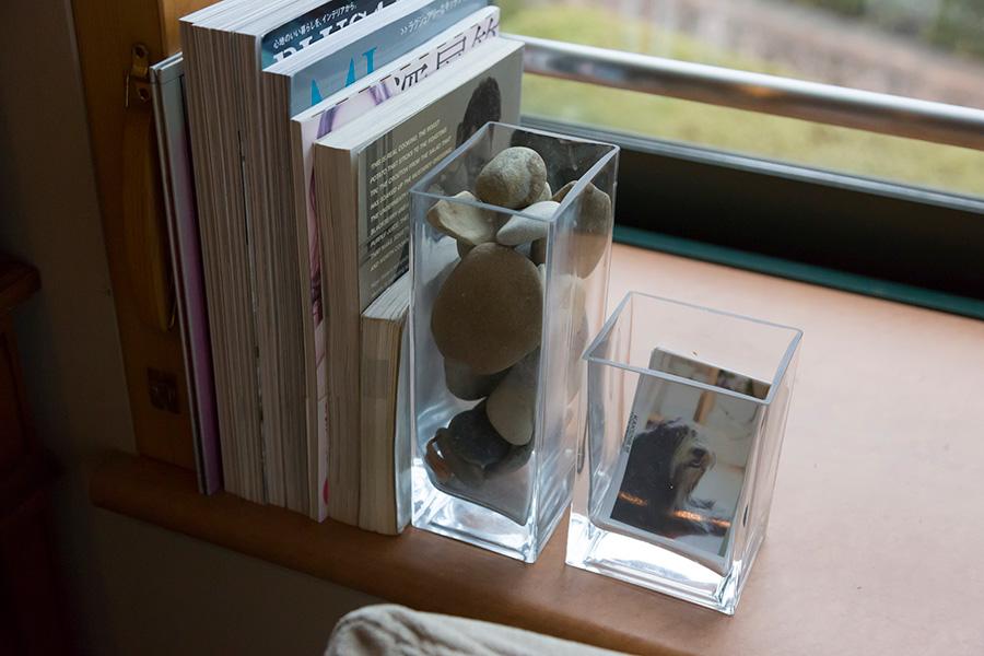 IKEAのフラワーベースに小石を入れてブックエンドに。右は愛犬の写真入れに。中身が簡単に入れ替えられて便利。