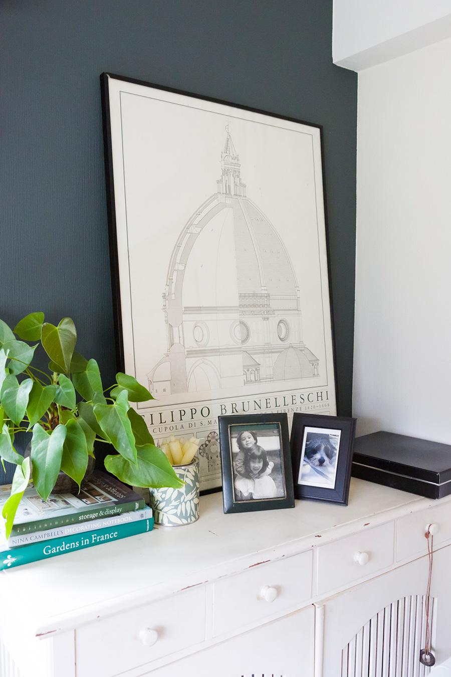 白い家具がチャコールグレーに映える。フィレンツェのドゥオモの絵や家族との写真などをディスプレイ。