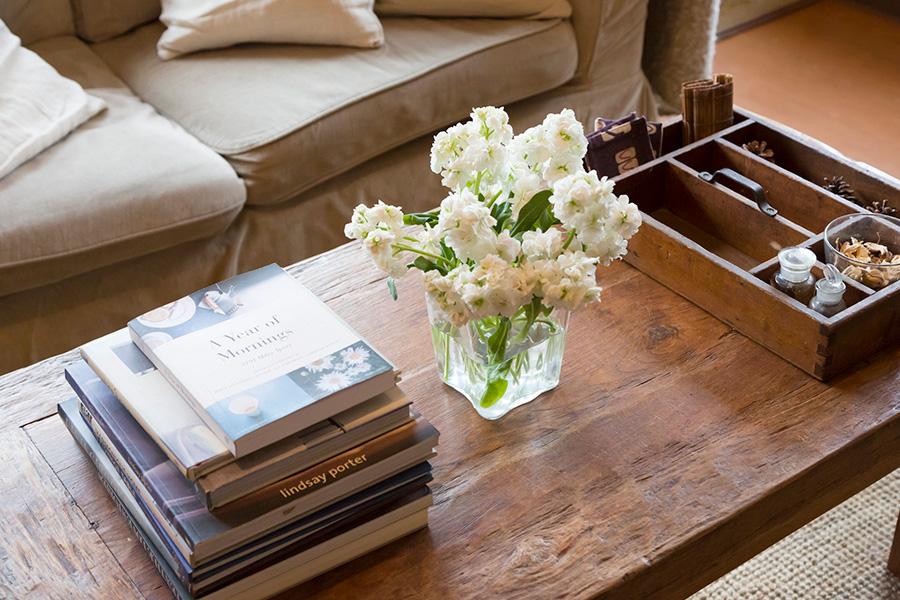 コーヒーテーブルの上はお気に入りの洋書、お花を欠かさない。右端の木箱はベルギーの花屋で入手。アンティークの瓶などをディスプレイ。