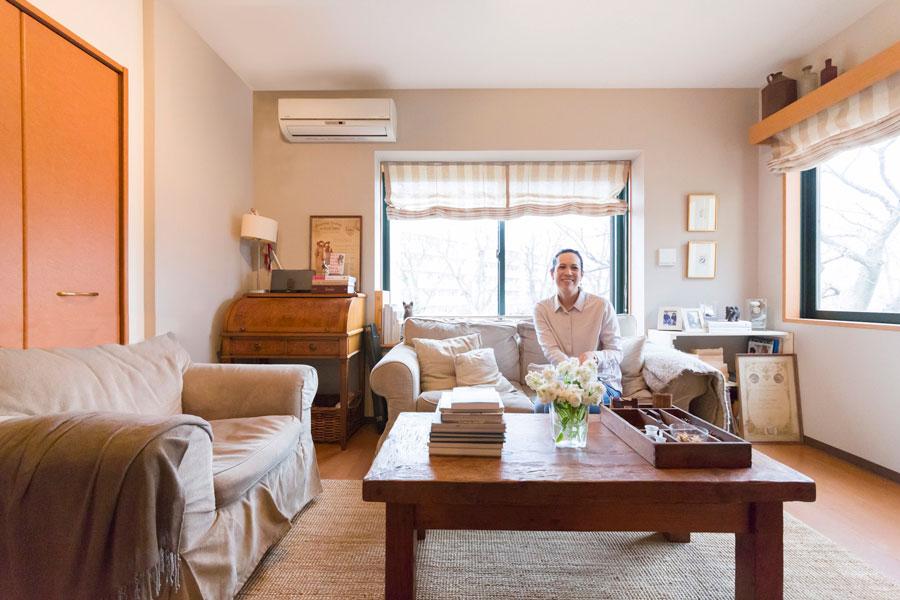 窓の向こうに桜並木が広がるリビングで。どっしりと重厚感のあるソファーはIKEA、コーヒーテーブルはIDÉE SHOP Pacific。