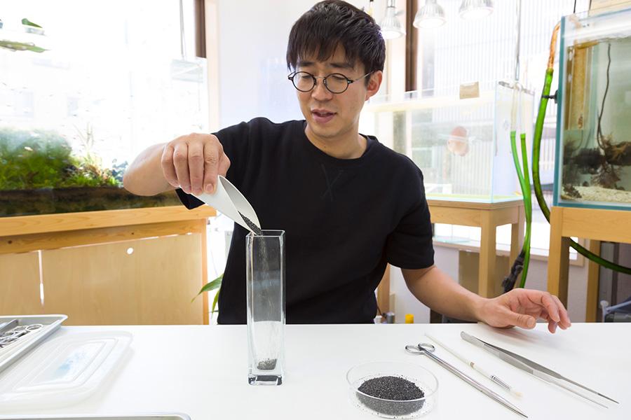 「SENSUOUS」の代表・早坂誠さんが1本植えをレクチャー。ベースの底に砂を敷き、水を入れ濁った部分を捨ててから、下の方の葉を処理した水草を植える。
