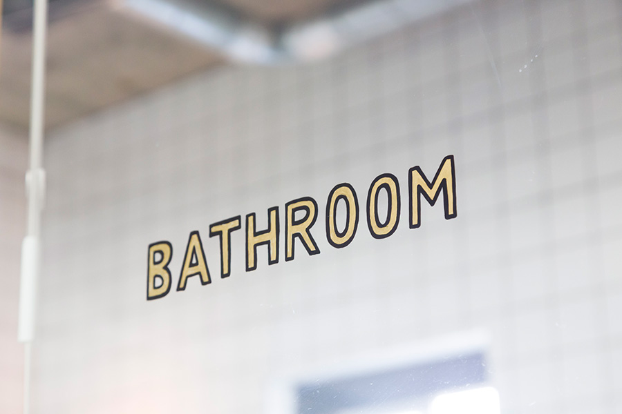 """ガラスのドアに金の飾り文字で""""BATHROOM""""をペイント。ステッカーでは出せない味。"""