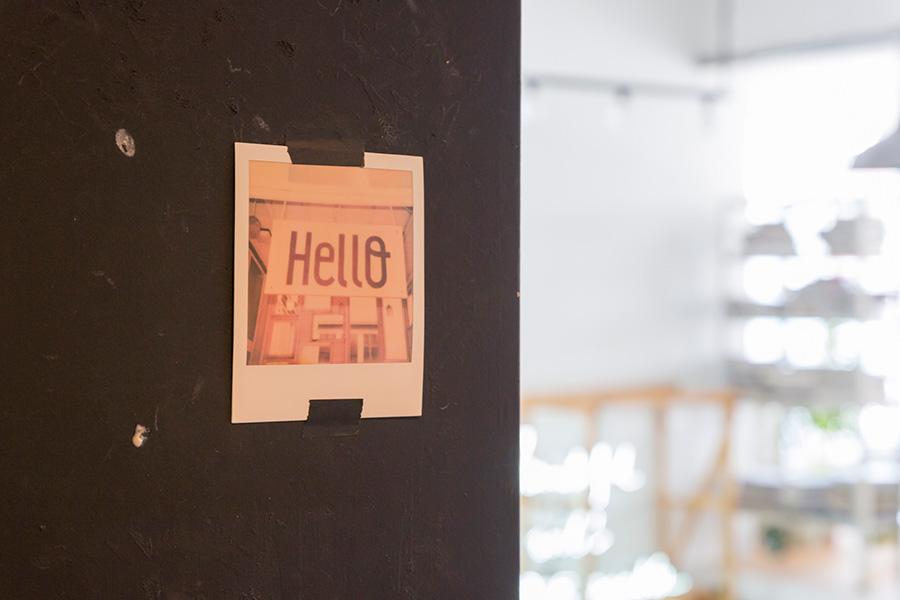 """玄関ドアを開けて室内に。扉にはキュートな""""Hello""""のポラロイド。"""