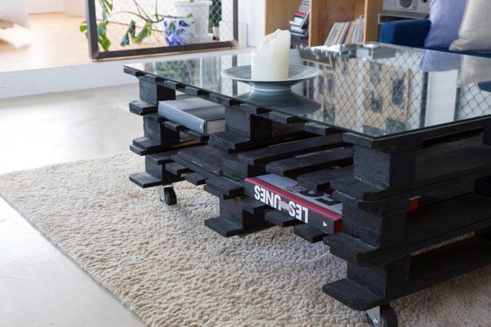 DIYしたローテーブル。パレット3段分を黒く塗り、キャスターをつけ、サイズオーダーしたガラス天板を載せた。
