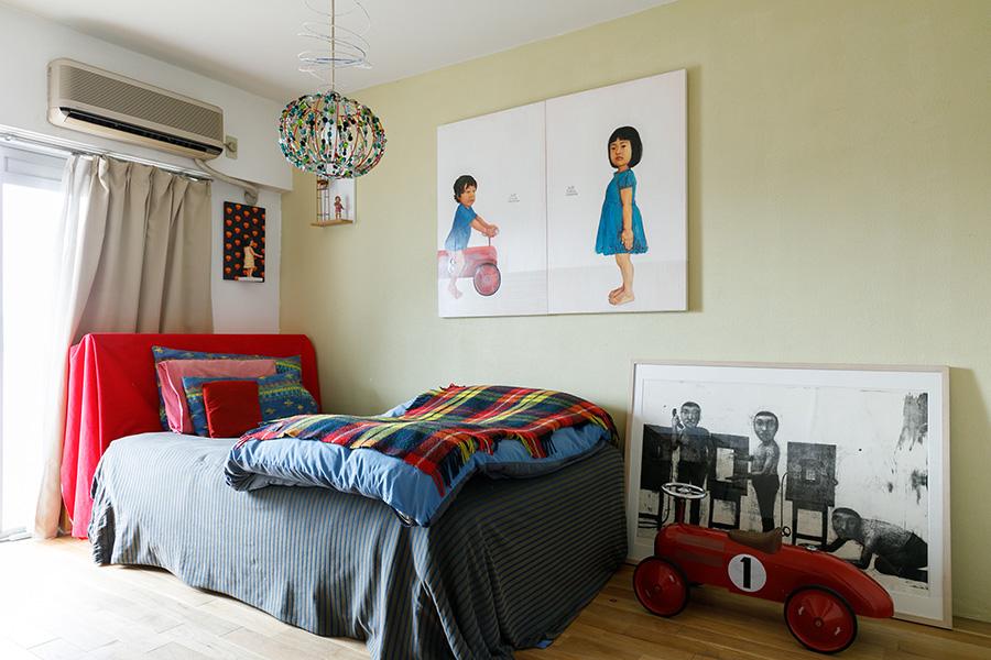 夫妻の寝室も一面だけ顔料入りの漆喰塗りに。ポップな照明は清香さんの手づくり。