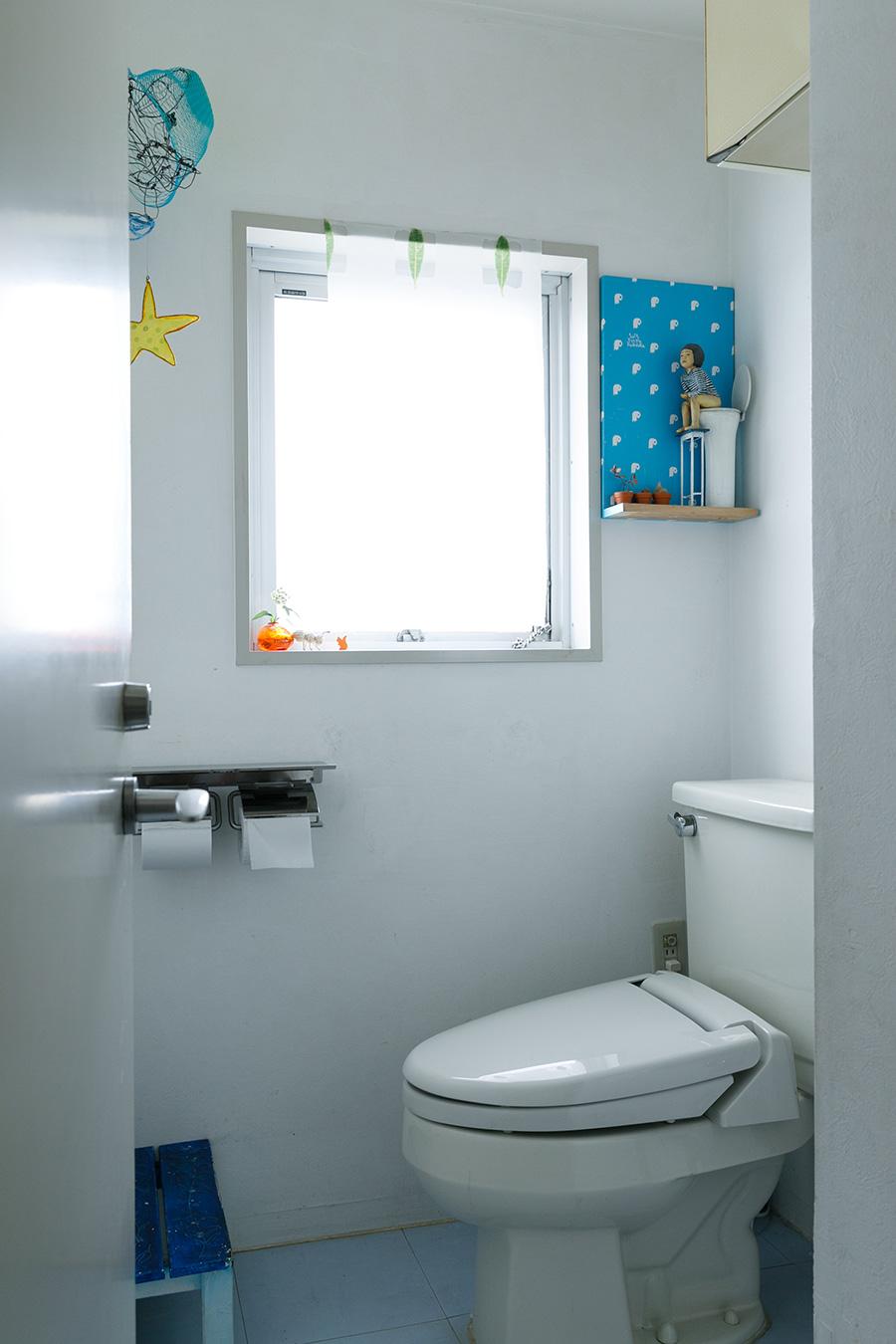 トイレの壁も漆喰を塗り、床にPタイルを張った。ここにも祐八さんやお子さまの作品がディスプレイされている。