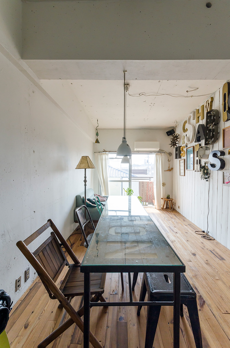 部屋に合わせて作ったダイニングテーブルは、パーティーにも大活躍。ペンダントライトはフランスの工業用のもの。