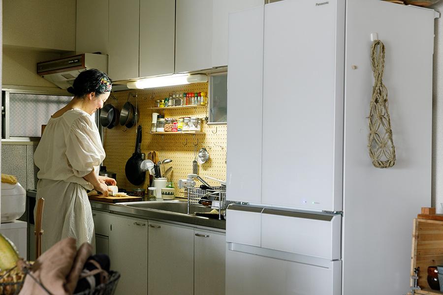 キッチンで料理をする長尾さん。窓を開けると風が通り匂いもこもりにくい。