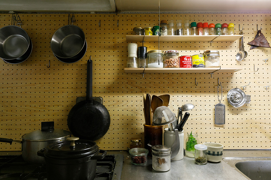 シンク奥の壁には穴あきの板を設置し、フックをつけてみせる収納に。