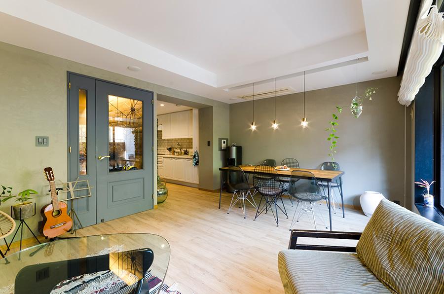 モスグリーンの塗装にグレーのドアが調和するリビングダイニング。天井の窪みを広げて高さを出した。