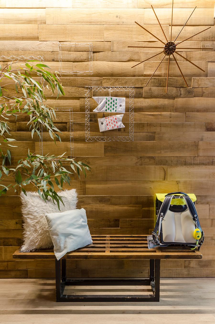 玄関の正面は、お子さんが作った工作なども活用してディスプレイスペースに。時計やベンチも徹さん作。
