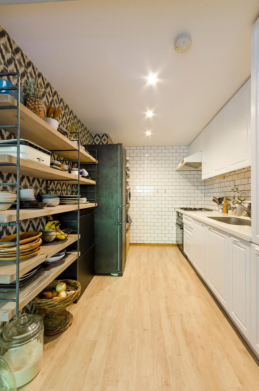 壁を取り外し、すっきりさせた使いやすいキッチン。キッチン台の面材や吊り戸棚は白で塗装。