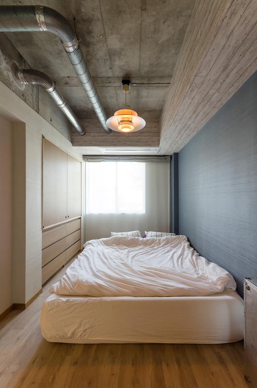 配管むき出しのベッドルームはどこか未来的な雰囲気。外せなかった右側の天井には壁紙を貼ったそう。