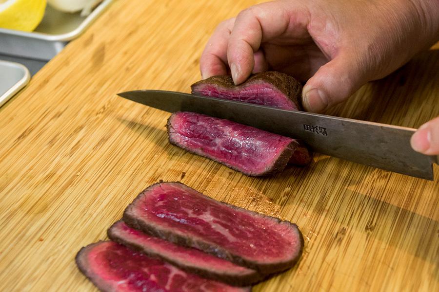 肉は繊維が縦に走っているものを買うのがポイント。肉の繊維を断ち切るように包丁を入れる。ギコギコするより、ゆっくりと押しながらカットし、切れたところをめくっては切ってはがしていく。