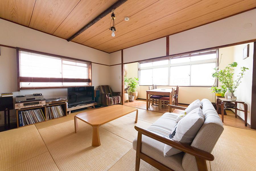 友人が何人集まっても受け入れ可能な畳敷きのリビング。天童木工のローテーブル。ソファはカリモクのもの。