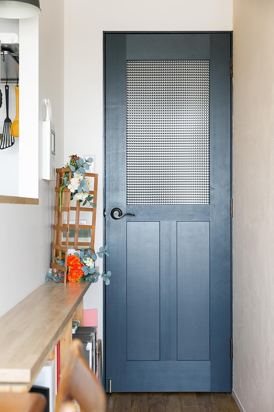廊下とLDKをつなぐドア。廊下に光を通すため、ガラス入りのものにした。色はアクセントになる暗めのブルーをチョイス。