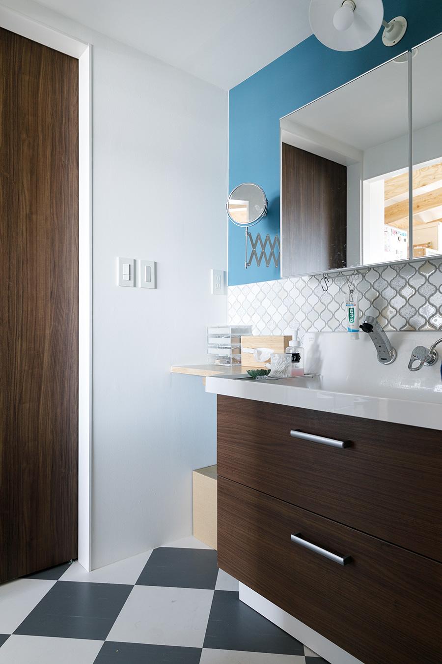 ブルーの壁、装飾性の高いタイル、チェック柄の床と、裕美さんのセンスが冴える洗面スペース。伸縮する便利な鏡はイケアのもの。