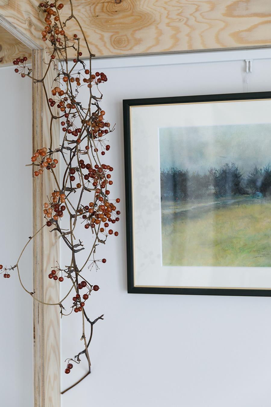 裕美さんが梁部分に引っ掛けた山帰来。朱色が木材と調和している。右の絵画は裕美さんのお父さまの作品。