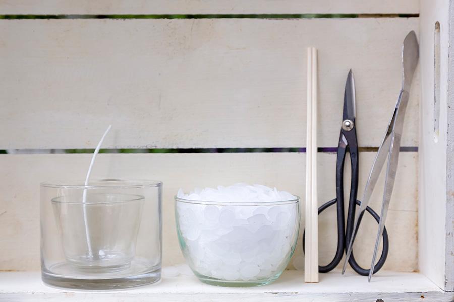 左から、ガラス容器(外側に飾りを、内側にアロマを入れる)。キャンドル用の芯と座金。パラフィンワックス。芯を立てるために使う割り箸。ハサミ、ピンセット。溶かしたワックスを流し込むための紙コップも準備しよう。
