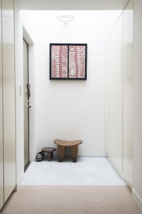玄関の天井には窓が設けられ、明るい日が差し込む。アボリジニのアートや、アフリカの木掘りの椅子をコーディネート。