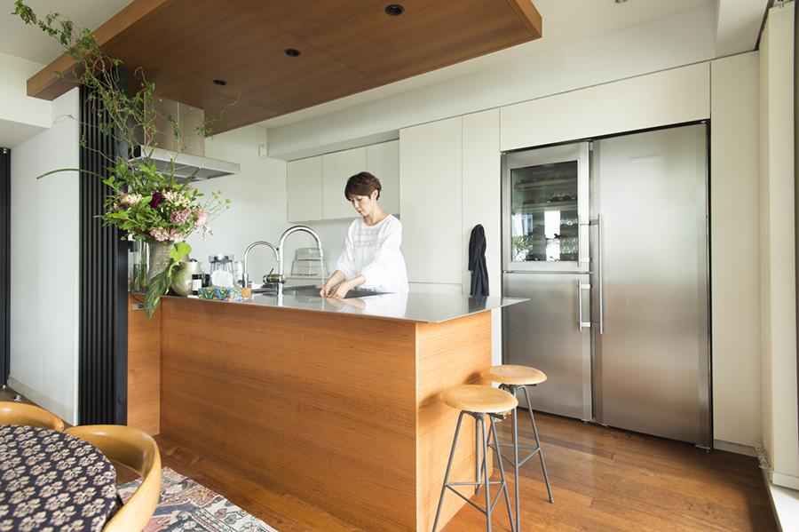 キッチンはアイランドでオープンに。天板は傷がついても味になるステンレスをセレクトした。ドイツの家電メーカー「LIEBHERR」の冷凍・冷蔵庫、ワインセラーは、デザイン性と機能性を両立。