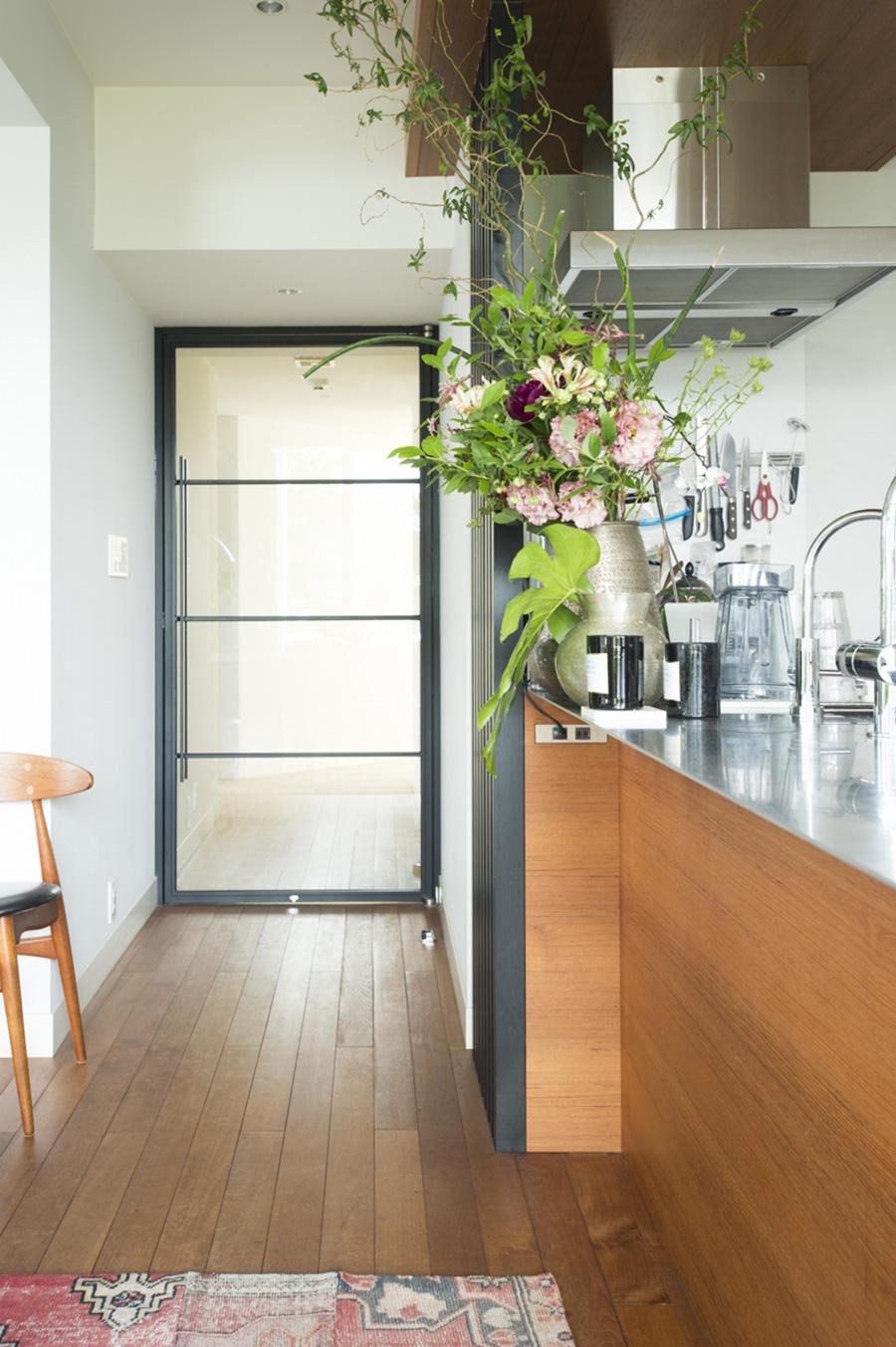 ガラスを使った黒枠のドアはオリジナルのデザイン。リビングの光と廊下側の部屋の光が通り抜ける。