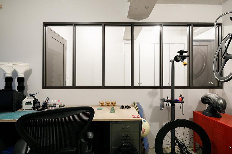 趣味の部屋と廊下の間の壁には大きな窓を設け、抜け感をもたせた。大きなデスクは「BISLEY」のロッカー2つに天板を載せてつくったもの。