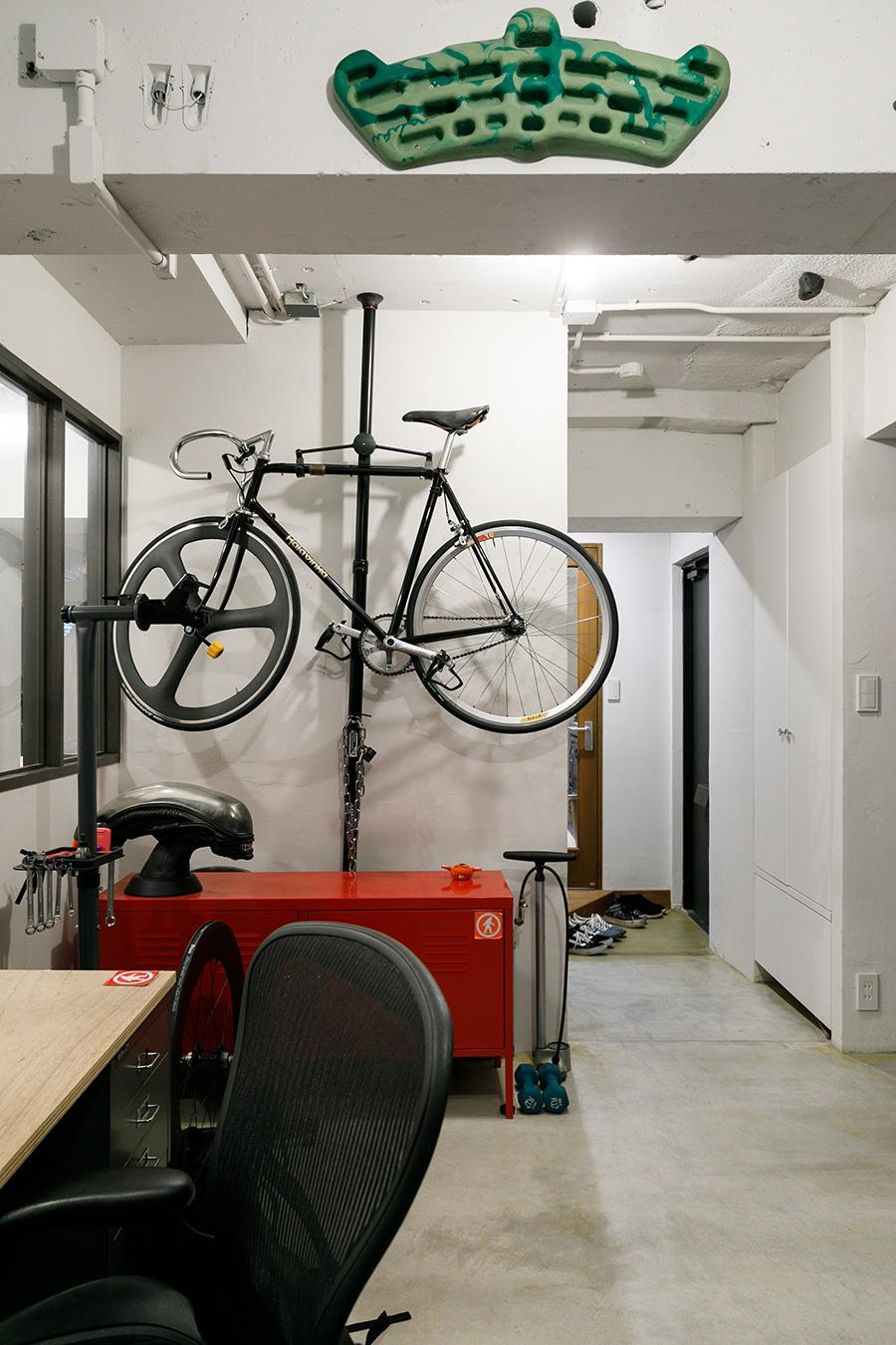 愛用の自転車はつっぱり棒タイプのラックにひっかけて。右手に見える玄関からすぐに出せるのも便利。