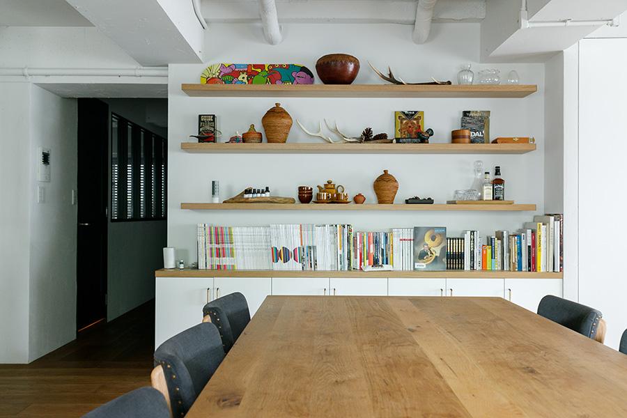 壁面には飾り棚と収納棚を造作。稲田さんが絶妙なバランス感覚で飾った小物たちが空間に彩りを添える。収納棚の中にはたくさんの食器と娘さんのおやつが入っているそう。
