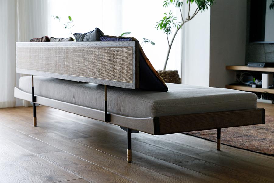 美しい佇まいのソファ。材はオークで背の部分は藤編み。座面にはマットレスに使うポケットコイルを入れていて、ゲストベッド代わりにもなる。