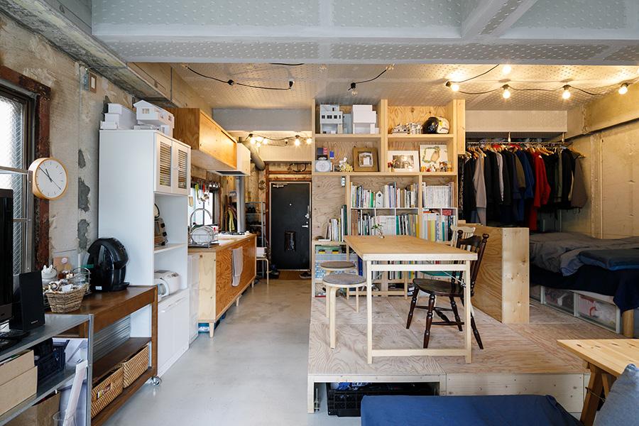 木製ユニットで空間を区切り、生活をつくる。手前がリビング、天井までつなげた棚の向こうが洗面スペースになっている。