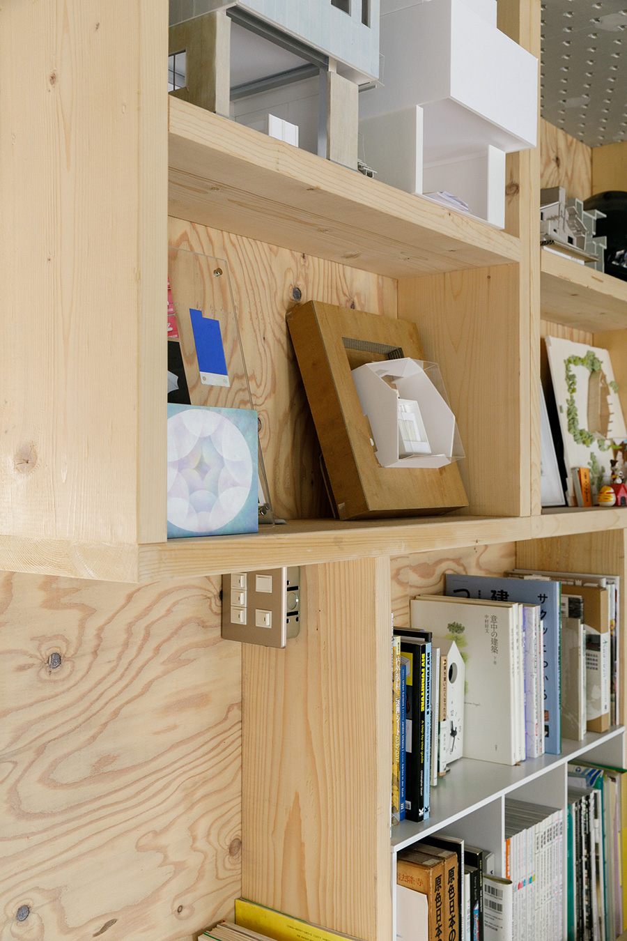 H型のユニットを縦横変えて組み合わせることで、多様な表情を持たせた棚。建築の模型や友人作家のアートが並ぶ。