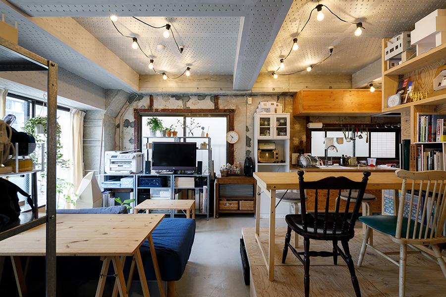 石膏ボードの天井と電照栽培用の照明が、ラフな壁や床と見事にマッチ。軽くて便利な折りたたみ式のダイニングテーブルはIKEA(廃盤)。左手前のシンプルなテーブルは原﨑さんのDIY。