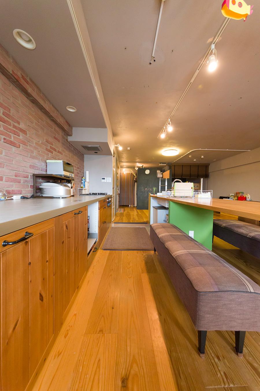 リビング側とシンク側の床に段差をつけることで、ダイニングテーブルが洗い物にもちょうどよい高さになる。キッチンの扉は『IKEA』のもの。