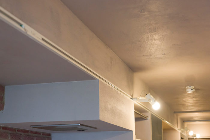 壁や天井はセルフペイント。5人がかりで丸4日間かかったそうだ。刷毛ムラがいい味を出している。照明のダクトレールが気持ちよくまっすぐに伸びる。
