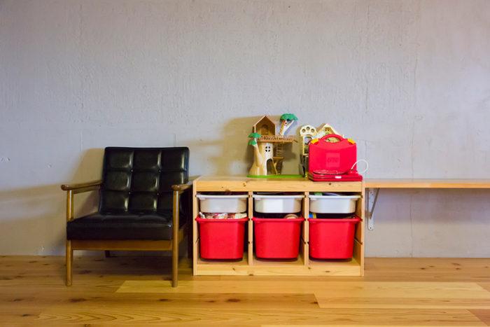 カリモクチェアの横にはオモチャを入れた棚。棚板はテレビ台として使われている。