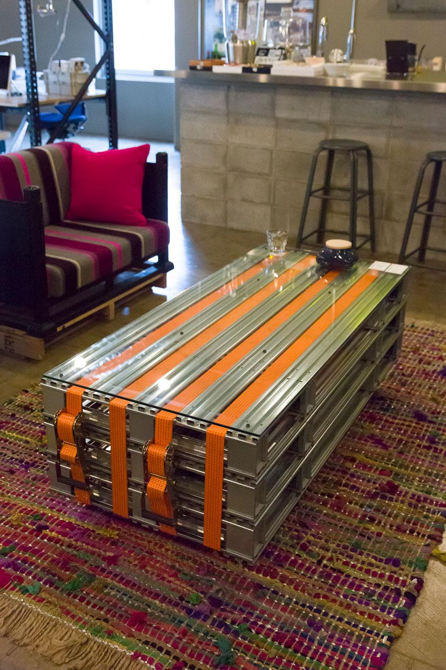 メタルのコンテナを3枚積み、ラッシングベルトで固定。その上にガラスの天板を置いた〈PALETTE TABLE METAL〉。サイドに本などを入れておくこともできる。