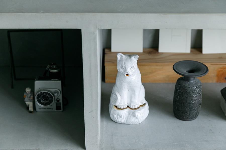 猫のモチーフのアスティエ・ド・ヴィラットの陶器など、素敵なオブジェが棚の中段に並ぶ。以前は本がズラリと収められていたが、どんこが背表紙に傷をつけるので本の収納は断念したそうだ。