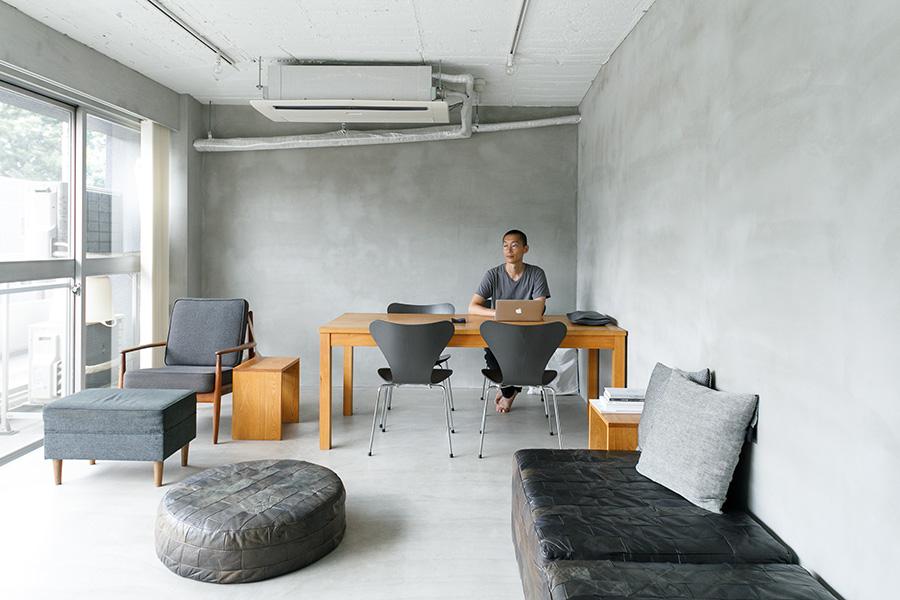 壁と床はモルタル、天井は白くペイントし、グレイッシュなトーンの室内に。家具の色数も抑えたモダンでシックなインテリア。