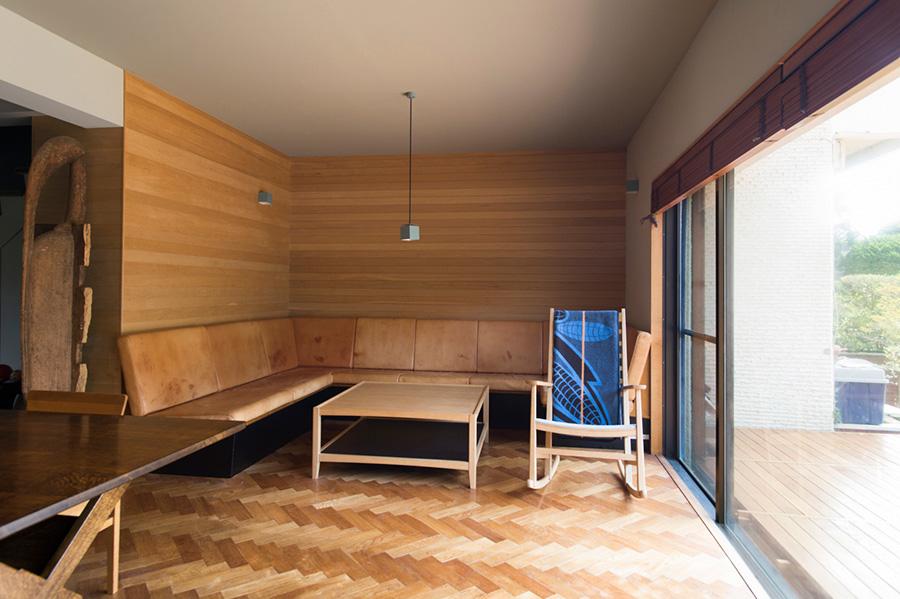 リビングにはL字型にヌメ革のソファーを造り付けた。素地仕上げの壁が自然な風合い。庭にはDIYでテラスを作ったばかり。