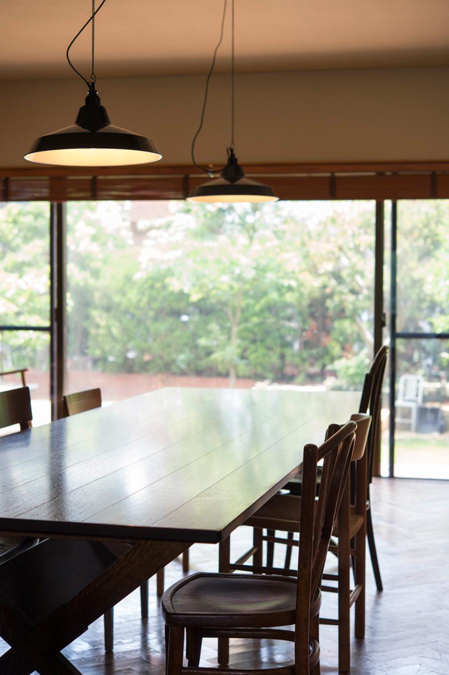 3mあるダイニングテーブルは、「スタンダード トレード」オリジナル。庭の緑を眺めながら食卓を囲む。