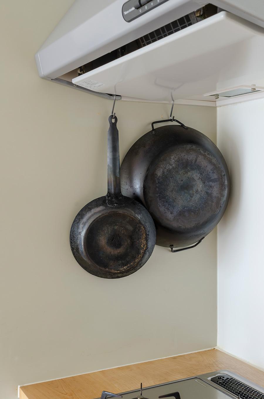 20年使っている鉄のフライパンは、使用後に水分を焼き切るので、熱いまま吊るせるよう工夫している。