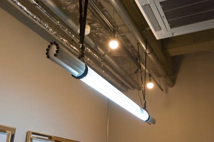 蛍光管のガラスの美しさを生かした〈BUNDLE LAMP〉。廃棄されたシートベルトを使って吊っている。